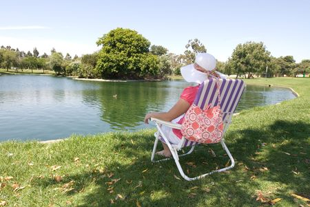 lakefront: A woman sits near the edge of a lake while relaxing on a Sunday morning.
