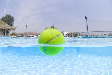 split level: A tennis ball floats on the surface of a swimming pool.  This shot was taken with an underwater camera at a split level of about 50 percent underwater and 50 percent abovbe water. Stock Photo