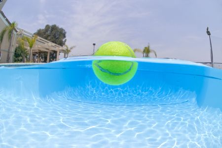 A tennis ball floats on the surface of a swimming pool.  This shot was taken with an underwater camera looking straight up at the surface of the water.