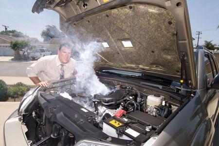 남자는 그의 흡연 차 엔진을 평가하려 할 때 매우 좌절하고 땀을 흘립니다.