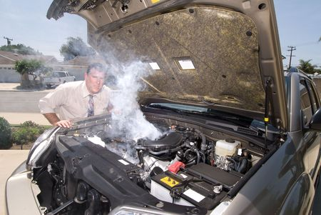 overheating: A man is very frustrated and sweaty while trying to evaluate his smoking car engine.