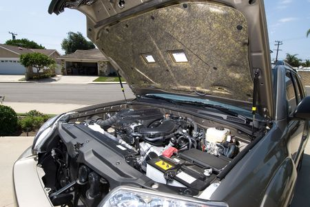 overheating: A broken down car with hood open for inspection.