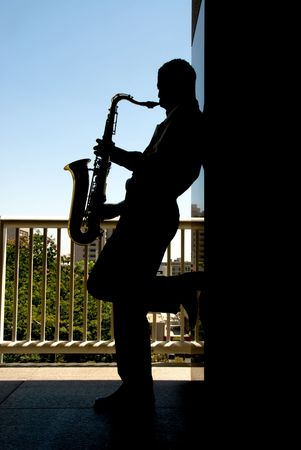 A saxophone player silhouetted against the bright daylight
