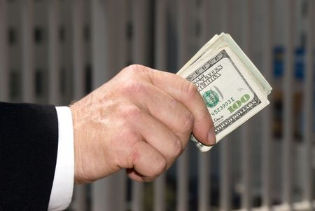 A businessman handing over a wad of cash. Stock Photo - 3820342