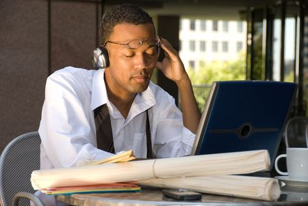 An executive engineer conducting work during his lunch hour decides to take a break and listen to some music.