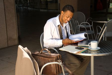 An African American businessman smiles as he is please with the information he is reading. Reklamní fotografie