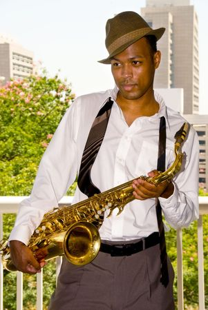 A saxophone player poses with his saxophone between musical sets. photo