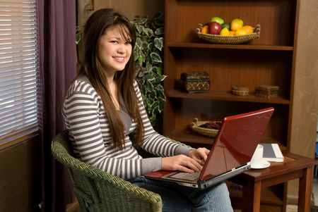 A young woman sits in her room using her laptop. Stock Photo - 4360668