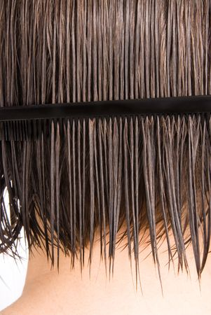comb hair: A woman combs her hair after a shower.