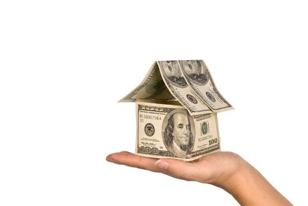 inference: A conceptual real estate and economic inference image showing a one hundred dollar bill house being held in the palm of ones hand.