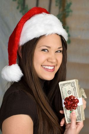 christmas savings: A woman displays her Christmas gift in the form of a stack of one hundred dollar bills. Stock Photo