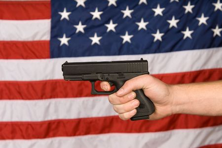 A man displays his semi automatic pistol against an American flag. Stock Photo - 4369161