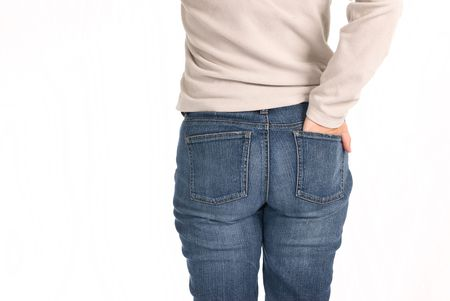 back pocket: A young woman stands with her hand in her back pocket isolated on a white background.