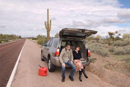 두 사람은 가스가없는 먼 사막 길의 측면에서 좌초되고 있습니다.