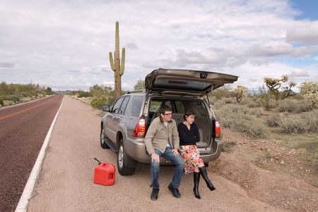 Two people are stranded on the side of a remote desert road out of gas. photo