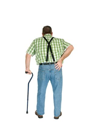 immobile: A man with back pain walks with the assistance of a cane.  Stock Photo