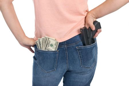 A woman is prepared to defend her cash with a semi-automatic handgun. Stock Photo - 4360664