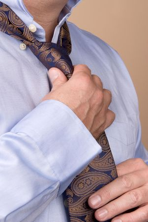 A man tying his necktie in preparation for work Stock Photo - 4360682