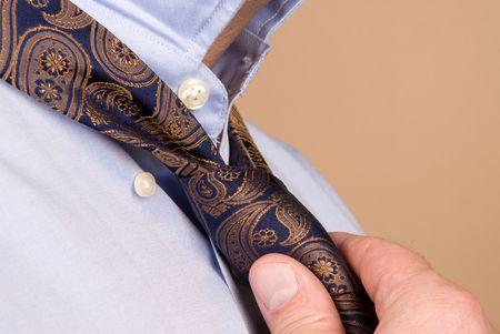 A man tying his necktie in preparation for work