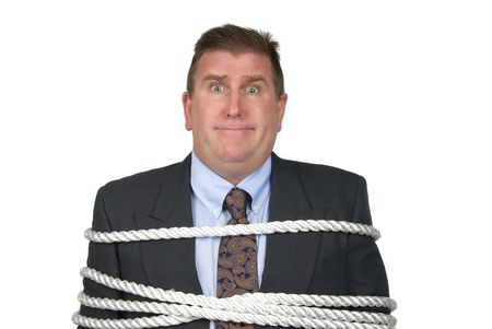 A businessman is tied up by his co-workers photo