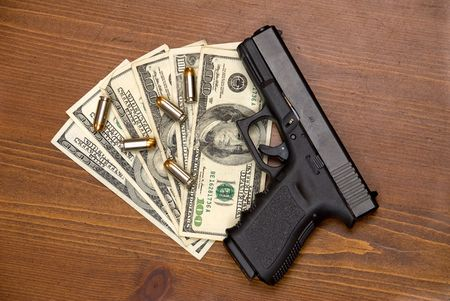 thievery: Bullets, cash and a gun on a table. Stock Photo