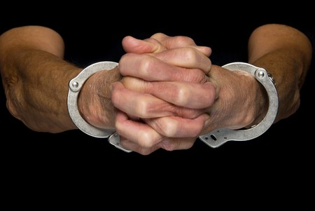 emphasize: A person holds out their cuffed hands.  Isolated with black clothing to emphasize the handcuffs.