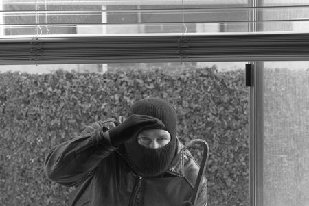 trespasser: A robber peers through a window to see if anyone is home. Stock Photo