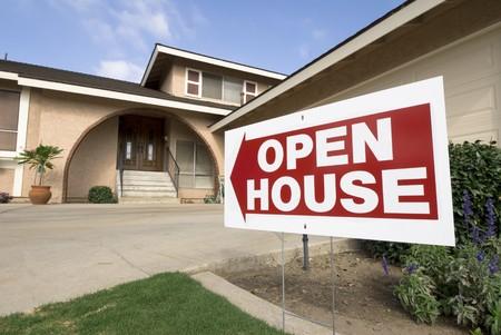 fachada de casa: Una casa para la venta muestra el signo de puertas abiertas en una tarde soleada. Foto de archivo