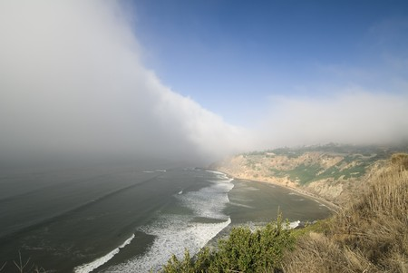 A huge weather front moves in quickly to engulf the sunny shoreline along the pacific coast in California.