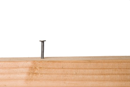 inference: A nail protrudes from a wooded beam and is isolated on a white background.  The image can be used for any tooling, fabrication or construction inference.