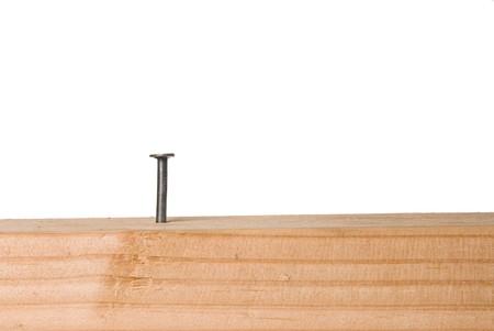 Een spijker protrudes uit een bosrijke bundel en is geïsoleerd op een witte achtergrond. De afbeelding kan worden gebruikt voor elk gereedschap, fabricage of de constructie inferentie. Stockfoto