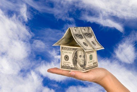 A conceptual real estate and economic inference image showing a one hundred dollar bill house being held in the palm of ones hand against a beautiful sky. photo