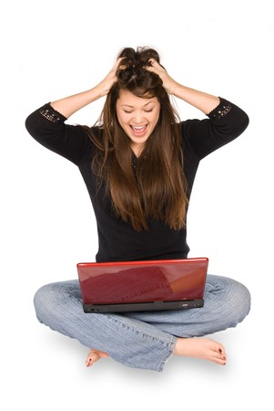 A young woman reacts in excitement as she views her laptop computer. photo