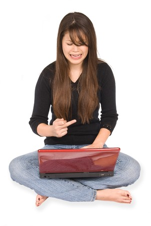 A young woman gets frustrated with her laptop and signals her middle finger in frustration. photo