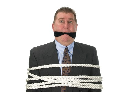 A businessman is tied up by angry co-workers. photo