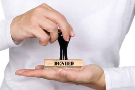 拒否された承認のスタンプを保持している女性