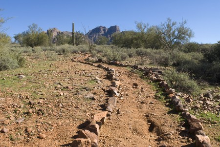 A dirt trail outlined by rocks leads deep into the Superstition Mountain range in the Arizona desert. Stock Photo - 4369438