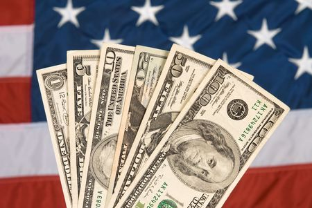 American currency against an American flag bakdrop. Stock Photo