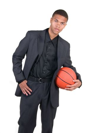 An African American basketball player poses in his business dress.  Image was shot against a lighted white backdrop and is not a cutout. Stock Photo - 4864122