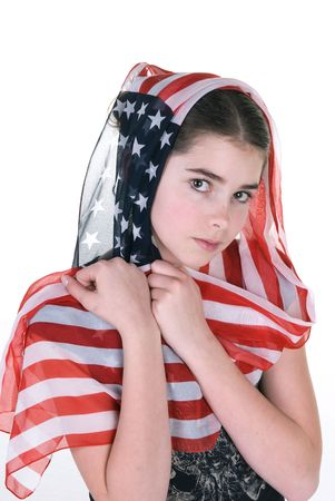 A young girl poses innocently with an American scarf covering her head. photo