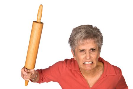 An angry grandmother is ready to swing her rolling pin to fend off unwanted bystranders. Stock Photo