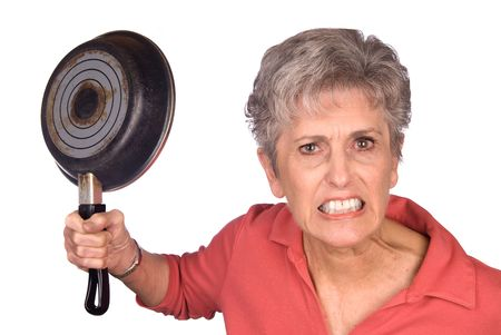 An angry mother threatens to swing her frying pan is a display of violent behavior. Image was shot against a lighted white background and is not a cutout.