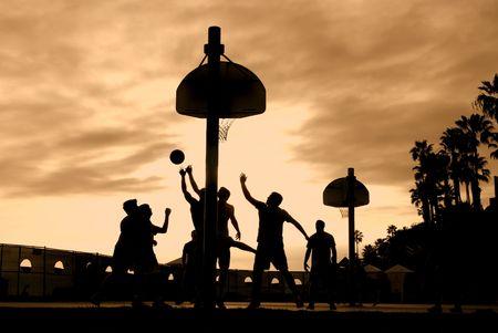 basketball shot: Basketball players at sunset play hard for the winning shot Stock Photo