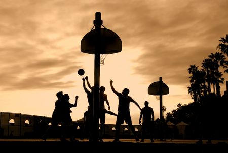 terrain de basket: Joueurs de basket-ball au coucher du soleil, jouer dur pour gagner la balle