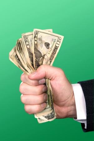 squeezed: Un empresario aprieta el pu�o lleno de dinero en efectivo.