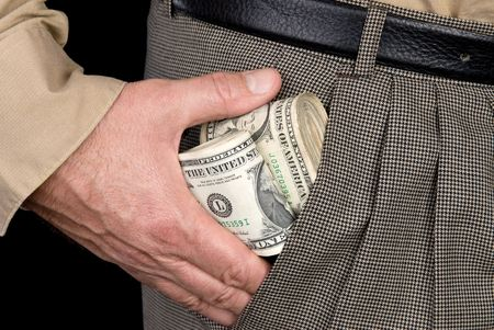 putting money in pocket: A man stuffs wads of cash into his pocket. Stock Photo