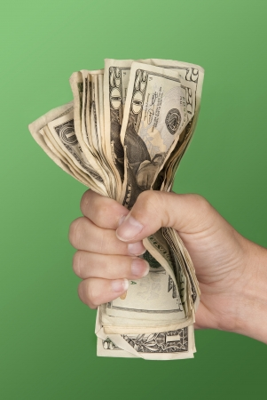 squeezing: A woman grips a wad of cash hoping she doesnt lose it.