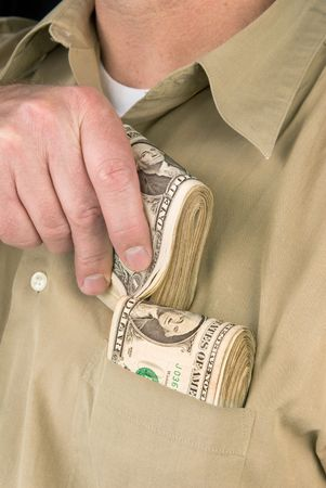A man places wads of cash into his shirt pocket.  For use with any kind of inference such as drug dealing; gambling; stealing; shopping, etc. photo