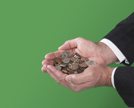 A man holds a pile of coins in his cupped hands.