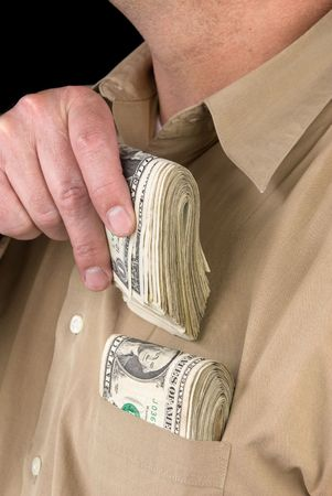 A man places wads of cash into his shirt pocket. photo